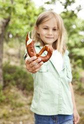 Girl holding bitten pretzel - MFRF000272