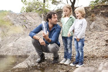 Father with two children with message in a bottle at lakeshore - MFRF000332