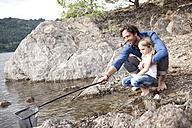 Father and daughter with dip net at lake shore - MFRF000265