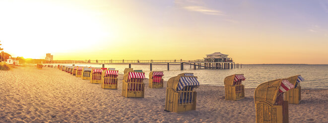 Germany, Niendorf, view to Timmendorfer Strand with hooded beach chairs and sea bridge - PUF000400