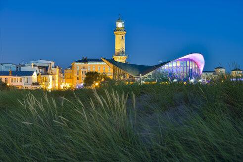 Germany, Mecklenburg-Western Pomerania, Warnemuende, Restaurant Teepott and old lighthouse at dusk - RJF000468