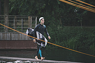 Young man carrying his wakeboard - MADF000506