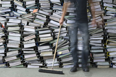 Man holding broom in front of pile of office files - ASF005666