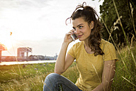 Germany, Cologne, young woman  sitting on a meadow near Rhine River telephoning - RIBF000144