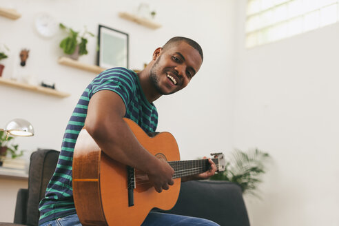Portrait of smiling man playing guitar at home - EBSF000847