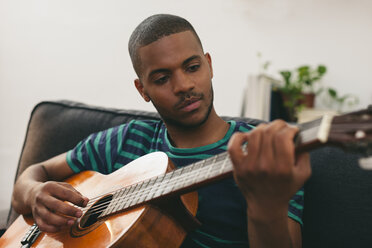 Portrait of man playing guitar at home - EBSF000848
