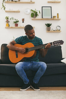Man sitting on a couch playing guitar - EBSF000849