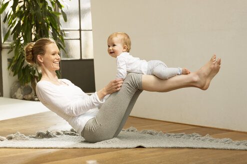 Woman balancing baby on her legs - ABF000629