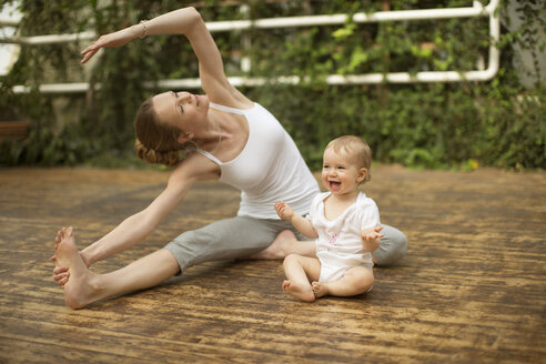 Woman doing yoga exercise while  baby having fun - ABF000632