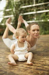 Woman doing yoga exercise while  baby sitting besides - ABF000636