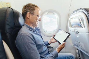 Mature man sitting on an airplane looking at his digital tablet - MFF001980
