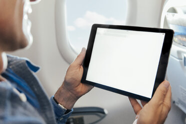 Man sitting on an airplane holding digital tablet - MFF001997