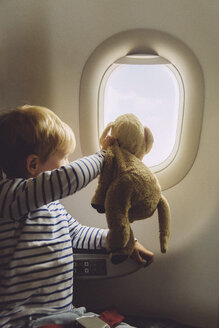 Little boy sitting on an airplane with his soft toy looking through window - MFF001989