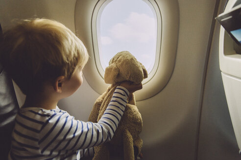 Little boy sitting on an airplane with his soft toy looking through window - MFF001990