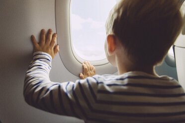 Little boy looking out of window while flying on an airplane - MFF001992