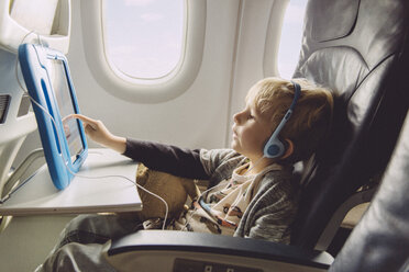 Little boy sitting on an airplane watching something on digital tablet - MFF001993