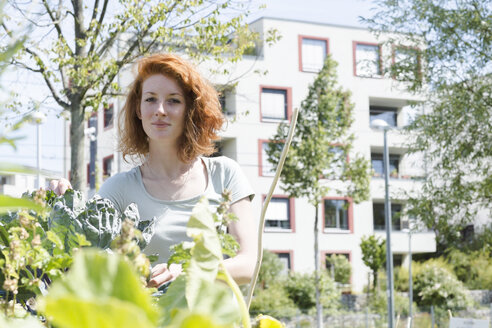 Young woman gardening, urban gardening - SGF001832