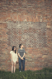 Teenage couple standing in front of a brick wall - MMFF000971