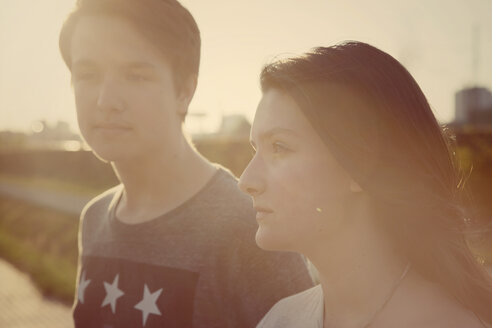Portrait of teenage couple at backlight - MMFF000974