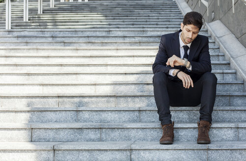 Portrait of young businessman sitting on stairs checking the time - PASF000007