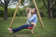 Mother sitting with her little daughter on a swing in the garden - MW000102