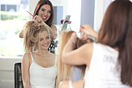 Mirror image of teenage girl and hairdresser at hair salon - TMF000024
