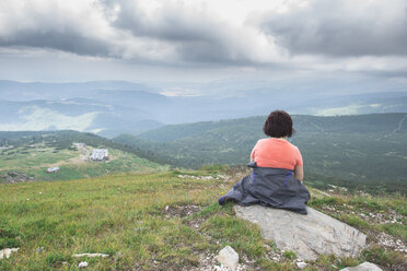 Bulgaria, Rila Mountains, back view of senior woman sitting on a rock  looking at view - DEGF000490