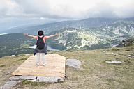 Bulgaria, Rila Mountains, back view of senior woman with outstretched arms looking at view - DEGF000491