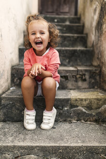Portrait of laughing little girl sitting on steps - MGOF000402