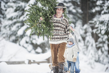 Austria, Altenmarkt-Zauchensee, happy man carrying Christmas tree on his shoulder in winter forest - HHF005383