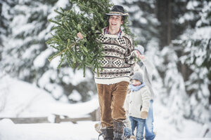 Austria, Altenmarkt-Zauchensee, happy man carrying Christmas tree on his shoulder in winter forest - HHF005383