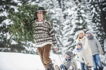 Austria, Altenmarkt-Zauchensee, man with Christmas tree and family together in winter forest - HHF005376