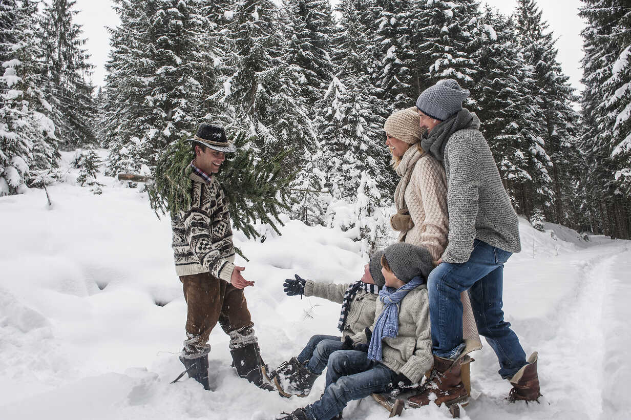 Austria, Altenmarkt-Zauchensee, man with Christmas tree and family together in winter forest - HHF005385 - Hans Huber/Westend61