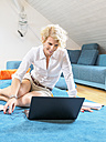 Portrait of smiling blond woman sitting on the floor using laptop - LAF001460