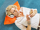 Portrait of blond woman with headphones using smartphone at home - LAF001473
