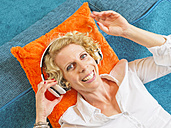 Portrait of smiling blond woman listening music with headphones - LAF001462