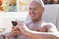 Smiling holidaymaker looking at his smartphone - ABAF001885