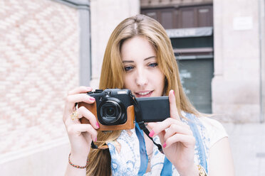 Spain, Barcelona, young woman taking a picture with digital camera - GEMF000303