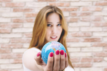 Young woman holding a globe in her hand - GEMF000305