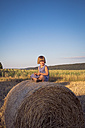 Smiling little girl sitting on straw bale - LVF003762