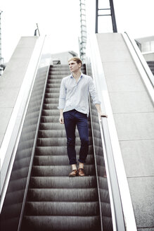 Young man standing on escalator - GDF000844
