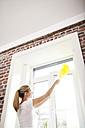 Woman dusting window - MFRF000348