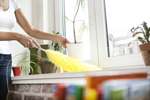 Woman cleansing windowsill with feather duster - MFRF000350