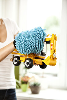 Woman dusting toy digger - MFRF000353