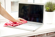 Woman cleansing laptop with duster - MFRF000374
