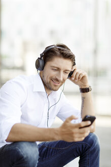Portrait of smiling man hearing music with MP3 Player and headphones - PESF000005