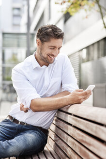 Portrait of smiling man sitting on wooden bench while looking at his smartphone - PESF000040