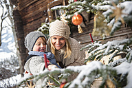 Austria, Altenmarkt-Zauchensee, mother and son looking at decorated Christmas tree in front of farmhouse - HHF005396