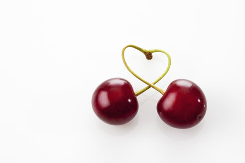 Stems of two sour cherries shaping a heart on white ground - CSF026091