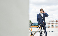 Businessman talking on the phone, holding bike - UUF005333